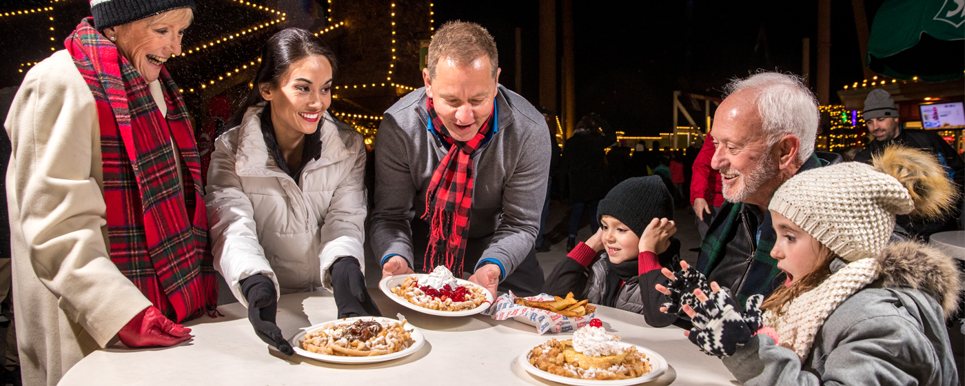 Family enjoying Kings Island's holiday activities & delicious food!