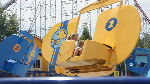 Young guests enjoy a ride on Woodstock Gliders, one of the most popular Kansas City attractions if you're looking for fun things to do with kids.